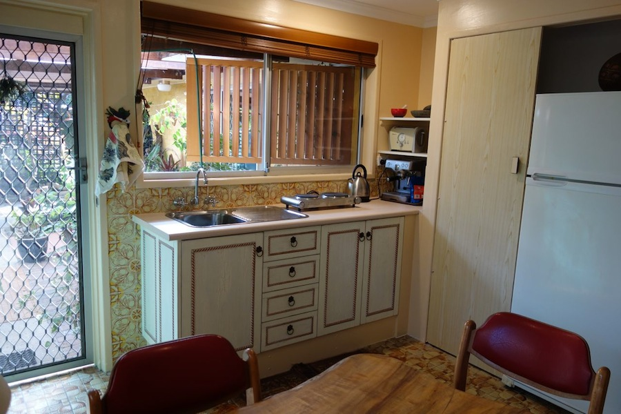 French country kitchen with two burner electric stove, toaster, expresso machine, small oven in cupboard, medium sized fridge.
